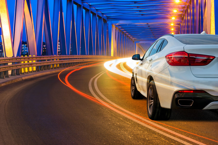 Generating energy by braking . Modern SUV driving across the bridge